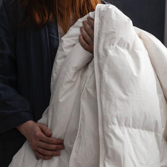 Девушка держит в руках теплое и пышное одеяло.