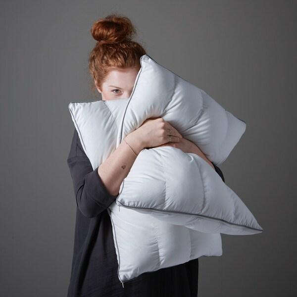 Девушка прижимает к себе пышные подушки