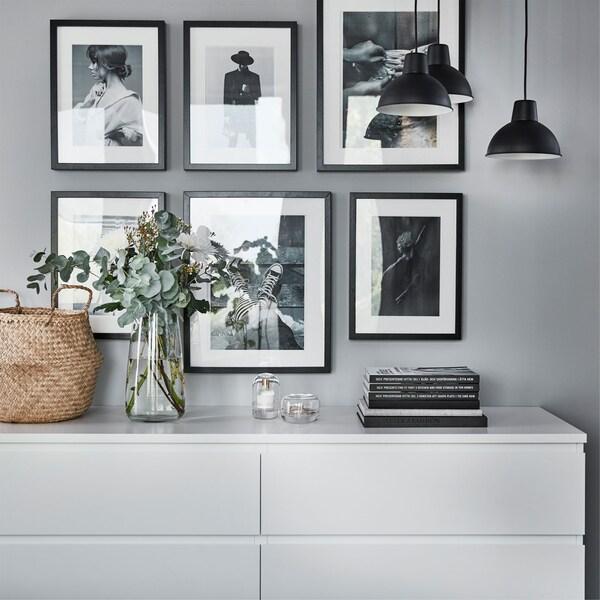 Bijela IKEA MALM komoda sa 6 ladica i vazom, knjigama i košarom uz zid na kojem se nalazi šest slika u crnim okvirima.