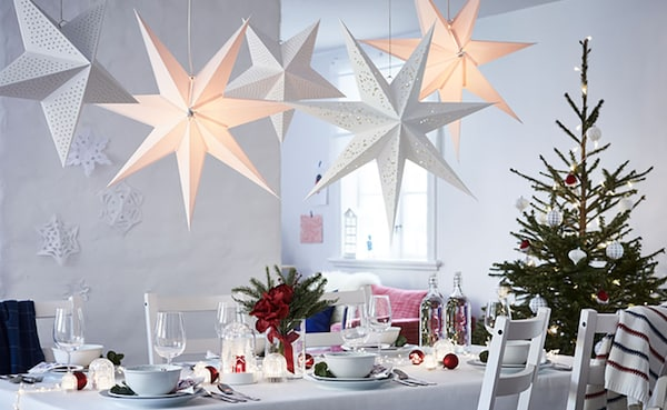 STRALA star pendant lights hang above a winter themed table setting. A dressed holiday tree sits in the mid ground at the end of the table.