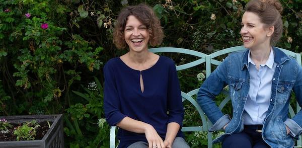 Die beiden Bloggerinnen von Klara & Ida auf einer Bank vor einer grünen Hecke.