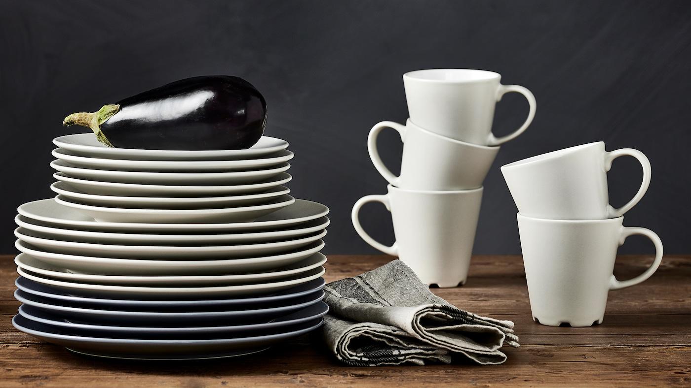 Die DINERA Becher in Beige/Weiß stehen auf einer Arbeitsplatte ineinander gestapelt neben einem Stapel beiger und grau/blauer Teller in verschiedenen Größen.