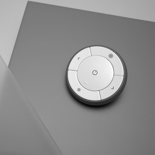 Die Fernbedienung haftet magnetisch an der Wandhalterung und wird mit Wandhalterung und Batterie mitgeliefert.