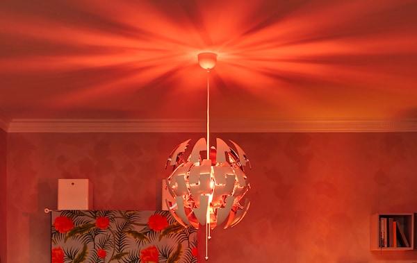Die IKEA PS Decken-Hängeleuchte mit roter Glühbirne im Wohnzimmer ist perfekt als Partybeleuchtung zum selber machen.