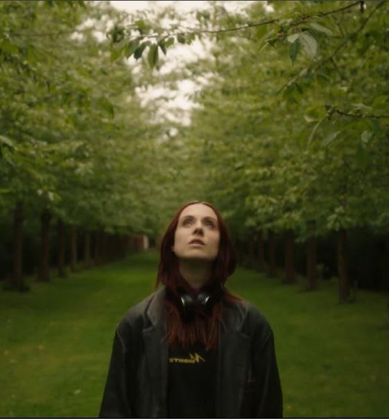Die Künstlerin MØ steht auf einer Wiese mit vielen Bäumen und schaut in die Luft.