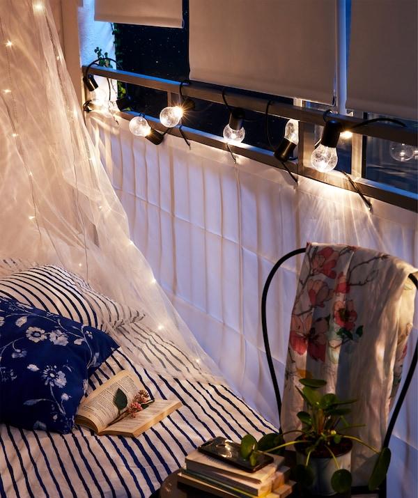 Die Seite eines Bettes am Balkongeländer, das mit DYNING Sichtschutz/Balkon weiß versehen ist, ergänzt duch Verdunklungsrollos.
