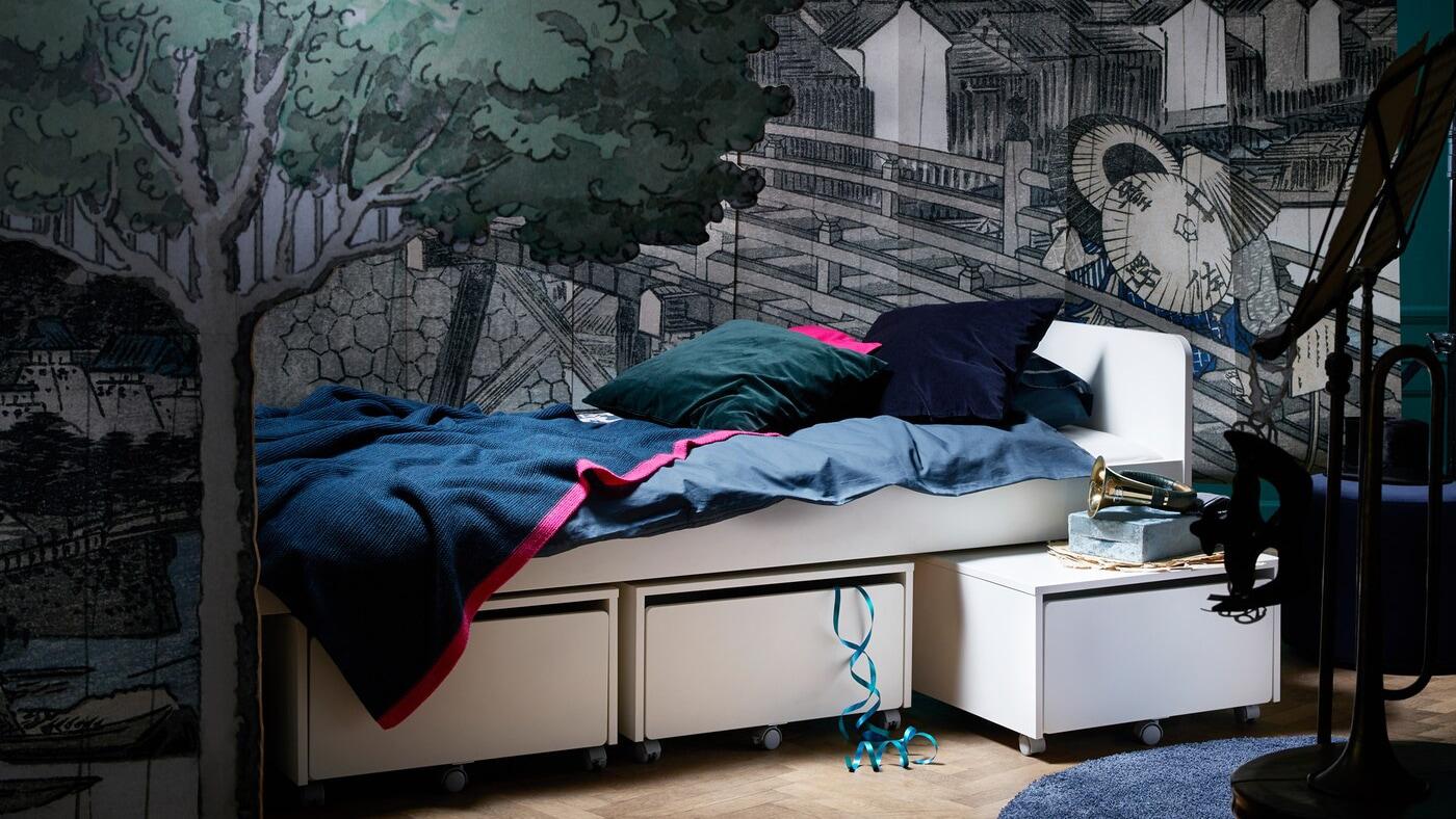 Die SLÄKT Serie besteht aus einem Bettgestell, einem Unterbett mit Aufbewahrung in Weiß und einer Aufbewahrung mit Sitzgelegenheit. So bietet sie Kindern verschiedene Unterbettmodule, die sich zum Entspannen und Abhängen nutzen lassen.