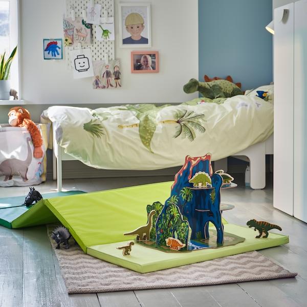 Die Welt der Dinosaurier mit Stofftierdinos ist auf einer faltbaren grünen Gymnastikmatte auf dem Fußboden nachgestellt. Im Hintergrund steht ein Bett mit grüner Bettwäsche.