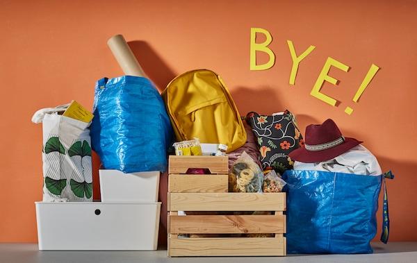 Die wichtigsten Dinge für die Uni, zusammengepackt in Taschen & Kisten an einer orangen Wand lehnend.