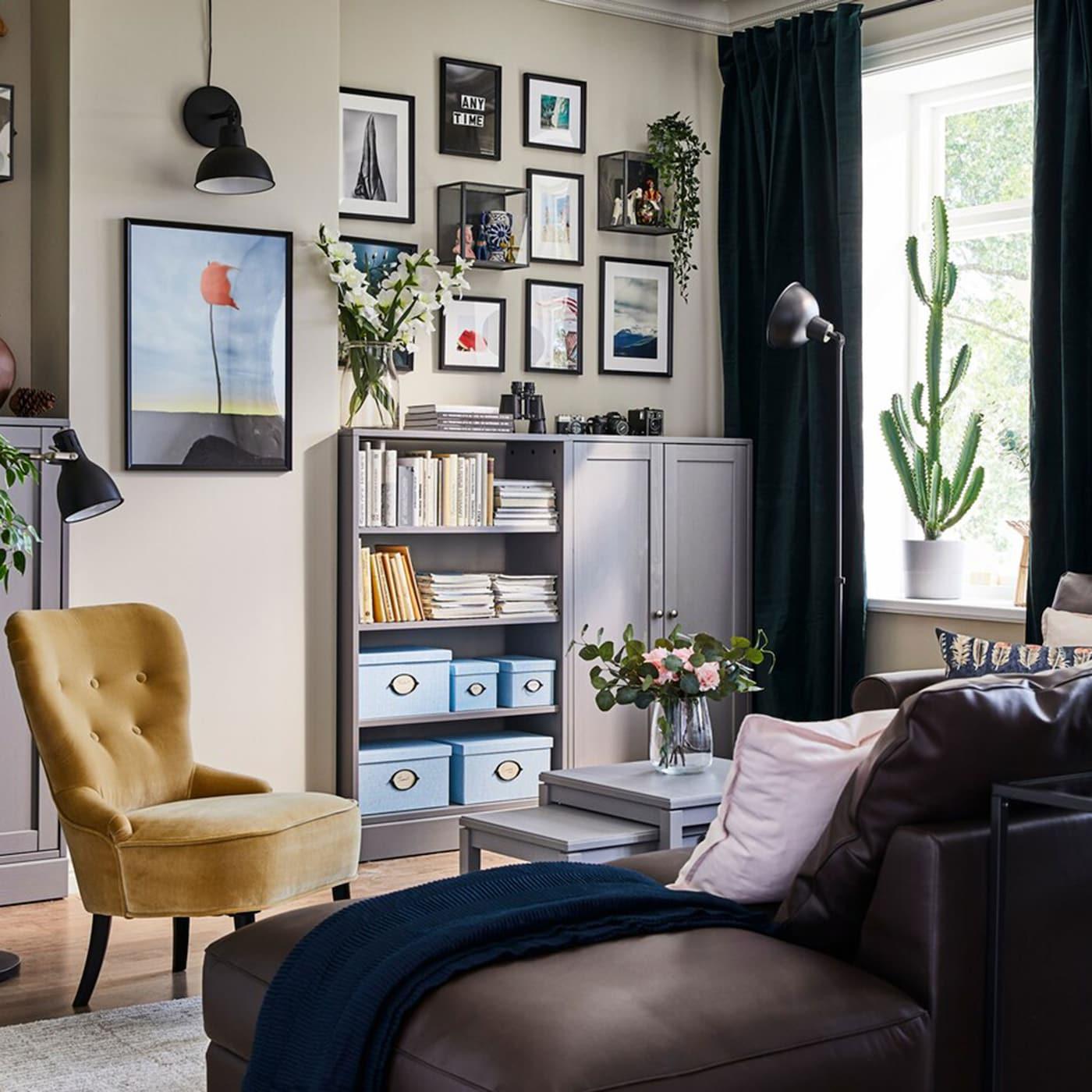Dieser farbenfrohe kleine Wohnraum steckt voller KNOPPÄNG Rahmen in Schwarz, BARKHYTTAN Objektpräsenter und einer HAVSTA Aufbewahrungskombination in Grau, um all die vielen Reisesouvenirs und Erinnerungsstücke unterzubringen und zu präsentieren.