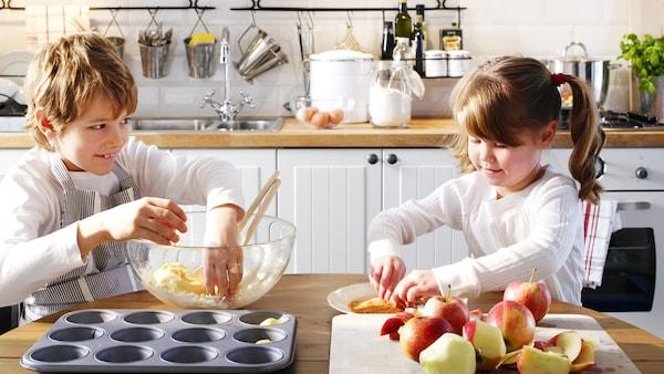Dievča a chlapec v kuchyne spoločne pečú koláč.