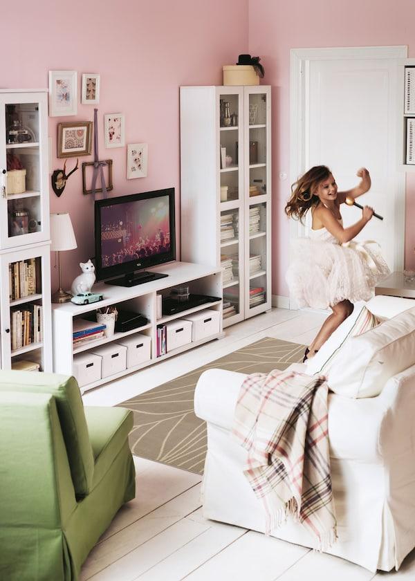 Dievča s mikrofónom spieva a tancuje na koberci pred pohovkou.