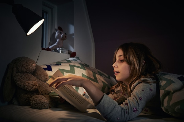 Dievča v pyžame si číta na posteli pri nočnom osvetlení s úspornou žiarovkou LED RYET.