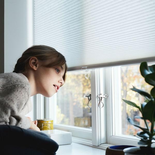 Dievča vo svetri sa pozerá z okna s čiastočne stiahnutou roletou.