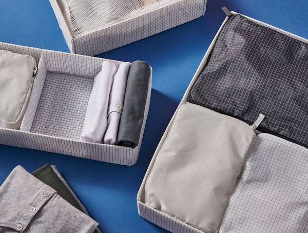 Diferentes bolsas RENSARE gardadas con orde en caixas de almacenaxe STUK, sobre unha superficie azul.