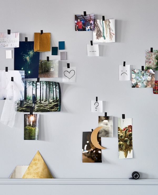 Different pictures of locations, foods, materials and colours taped to a wall and grouped by likes, dislikes and question marks to make a wedding moodboard
