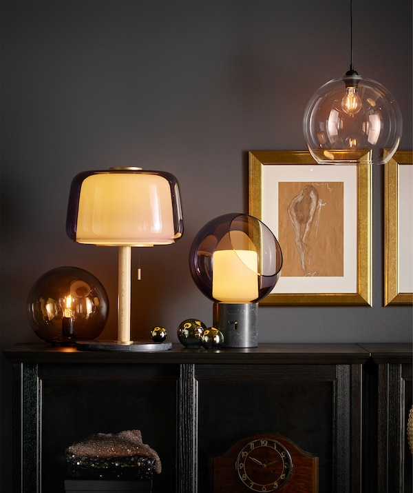 Different table lamps placed together on top of a cabinet in living room; most lamps with grey glass and yellow, warm light.