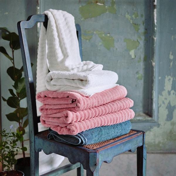 Différentes serviettes en gris, rose et blanc empilées sur une chaise en bois gris foncé, posée contre une porte rustique en bois gris-vert.