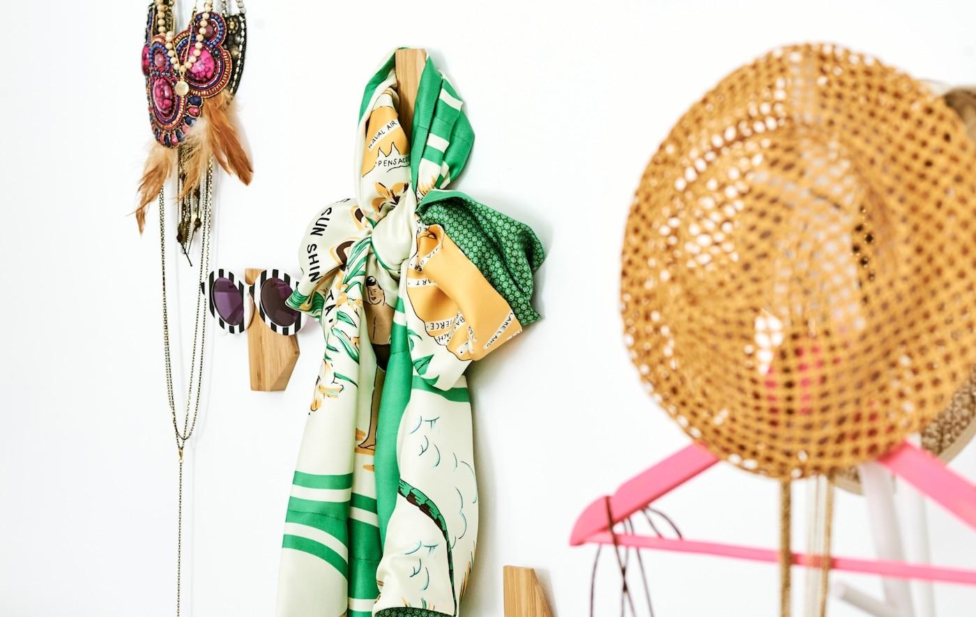 Différents accessoires vestimentaires accrochés au mur sur des crochets asymétriques: des lunettes de soleil, un foulard, des colliers et un chapeau de paille.
