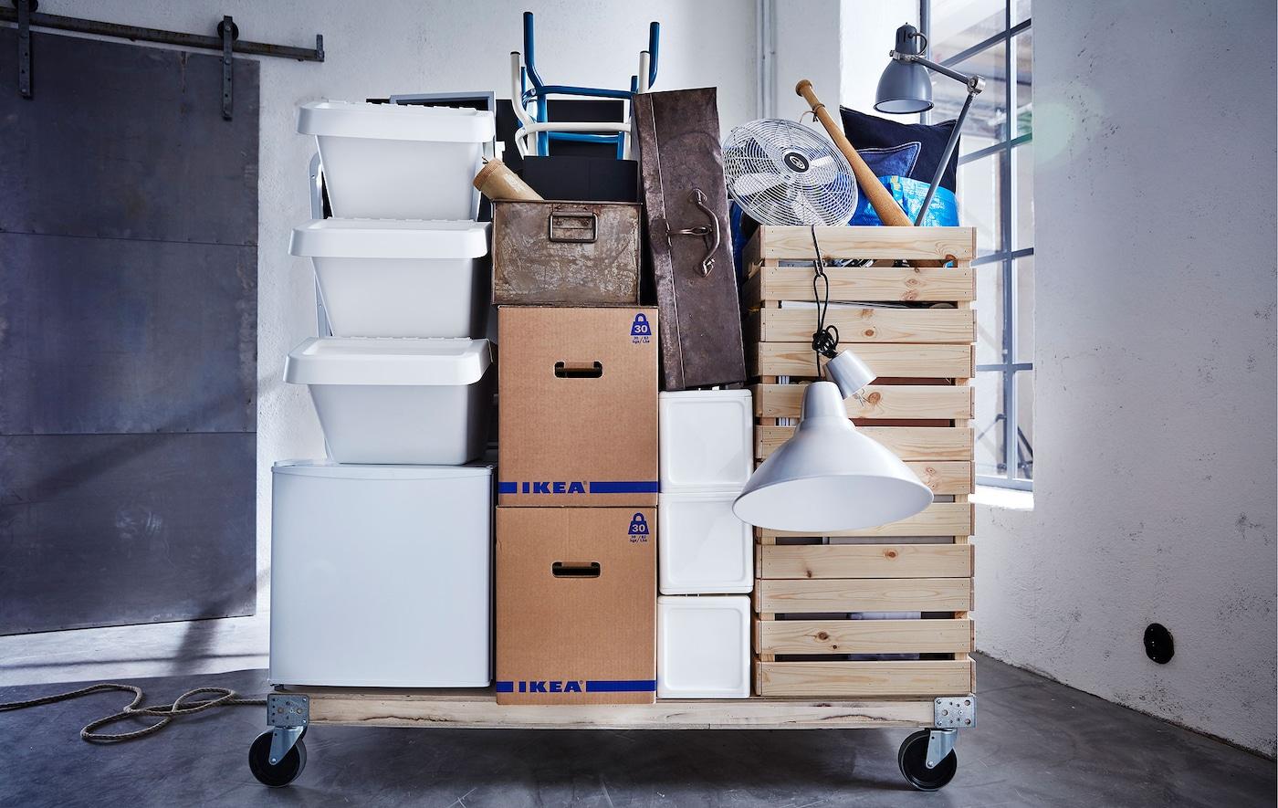 Différents essentiels de déménagement et des boîtes JÄTTENE empilées sur une palette en bois sur roulettes, dans une pièce vide.