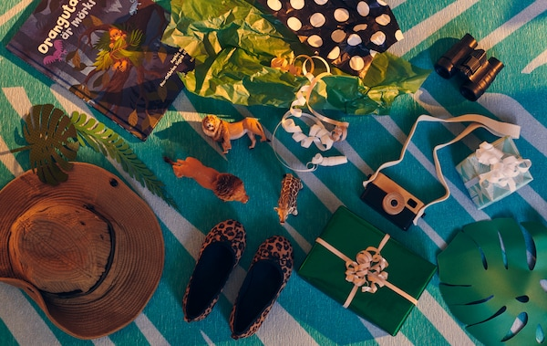 Différents jouets et cadeaux, certains emballés, d'autres non, sur le thème de l'exploration et de l'aventure sur le tapis GRACIÖS.