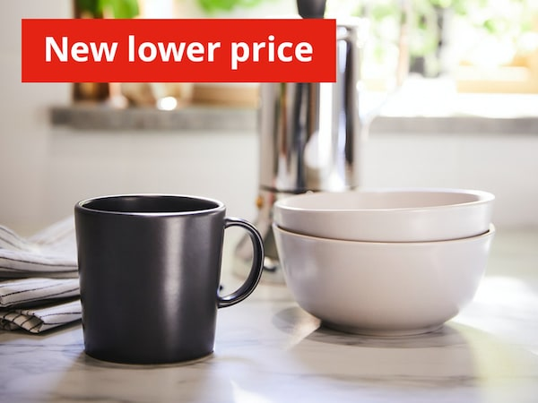 Dinera black mug and 2 stacked white bowls on table  with New Lower Price banner