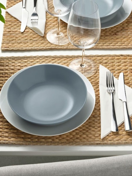 DINERA tableware on a white table with wine glasses, cutlery and placed on a natural UNDERLAG place mat