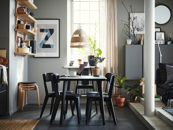 Dining area with a table, four chairs and a highchair in black, open shelves in ash veneer, four stools and beige curtains.