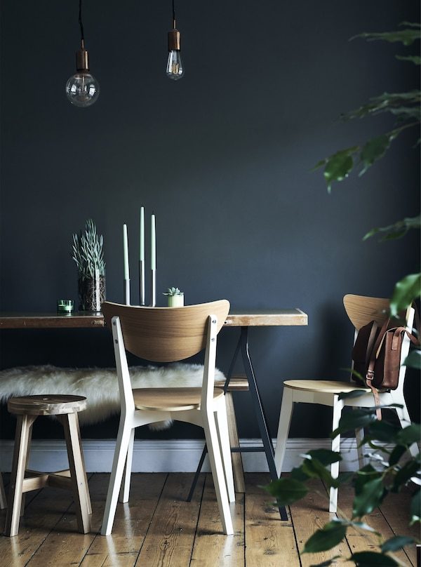 Dining chairs and table against a dark blue wall.