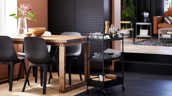 Dining room with anthracite chairs, a stained oak veneer table, black storage, a jute rug and a trolley with tableware.