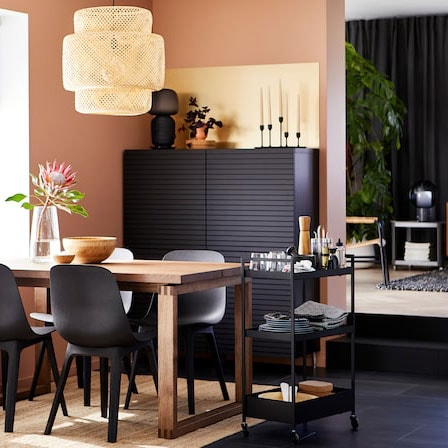 Dining room with anthracite chairs, a table in solid oak wood veneer, black storage, a jute rug and a pendant lamp in bamboo.