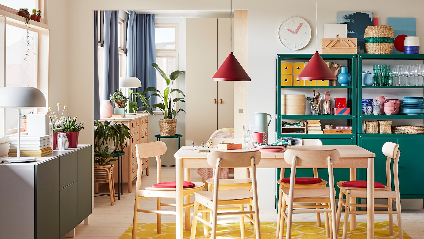 Dining room with table and chairs in birch, a yellow rug, a white/gray-green storage combination and dark red pendant lamps.
