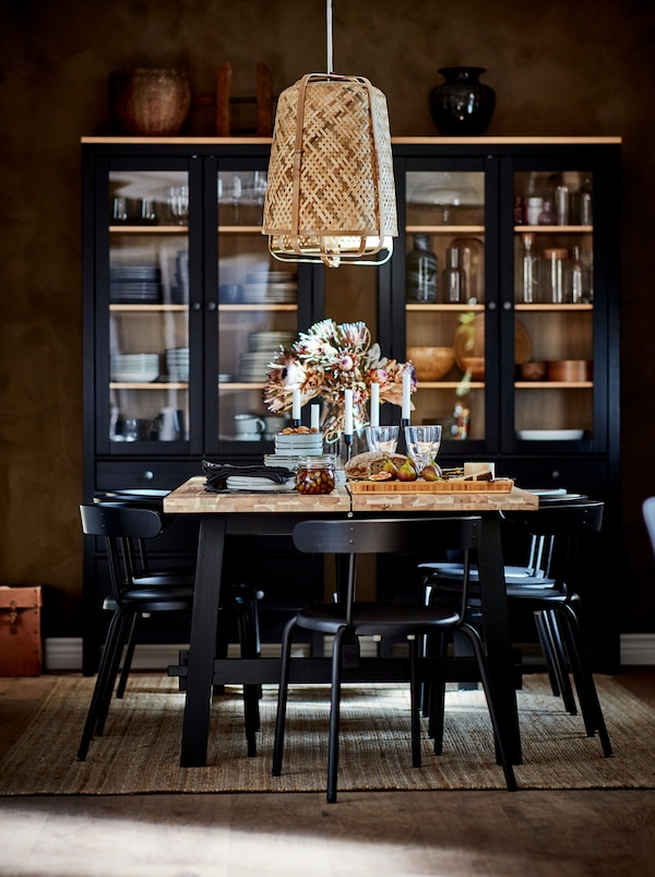 Dining table being festively set under a KNIXHULT pendant. Dark glass-door cabinets with table accessories by the far wall.