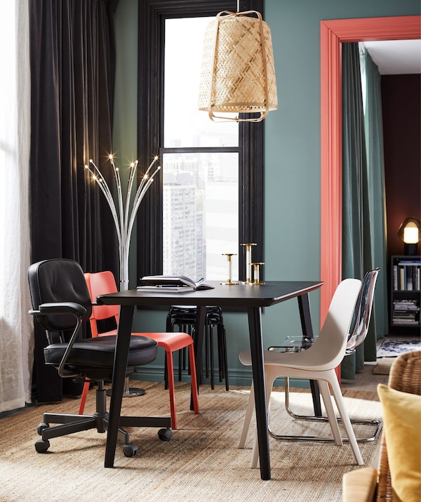 Dining table in living room with odd chairs. Colour palette of rich colours and brighter accents; decorative lighting.