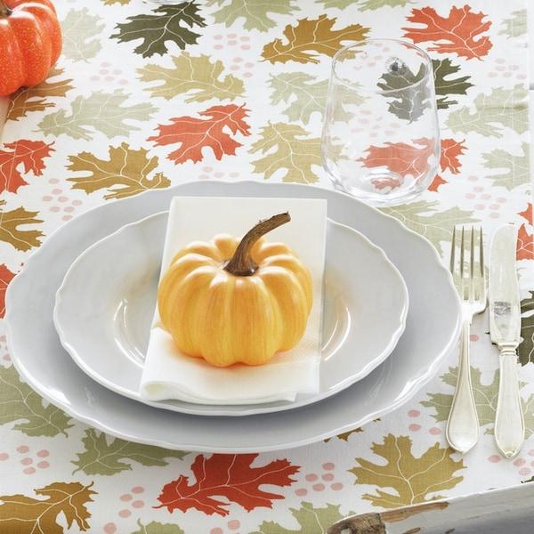 Dining table place setting on HÖSTPROMENAD table runner surround by HÖSTPROMENAD decorative pumpkins