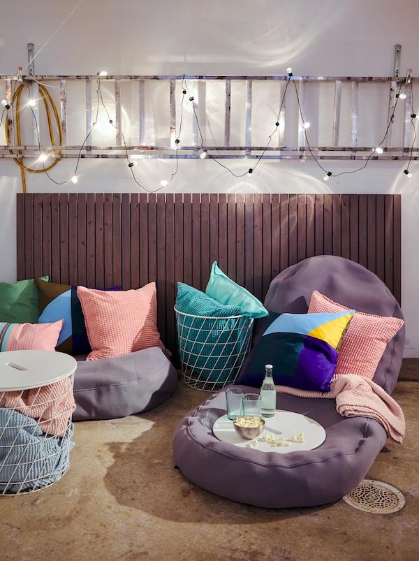 Dio betonskog poda prekrivenog BUSSAN vrećama za sjedenje i ukrasnim jastucima s još više tekstila u KVISTBRO stolovima za odlaganje.