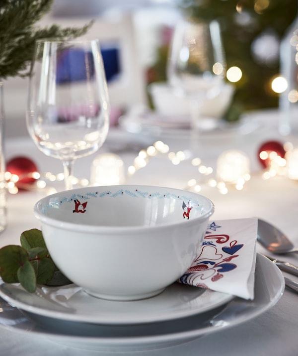 Dio blagdanskog stola za jednu osobu. Više tanjura, rasvjetni lanci na stolu, zelene zimske dekoracije, čaša za vino.