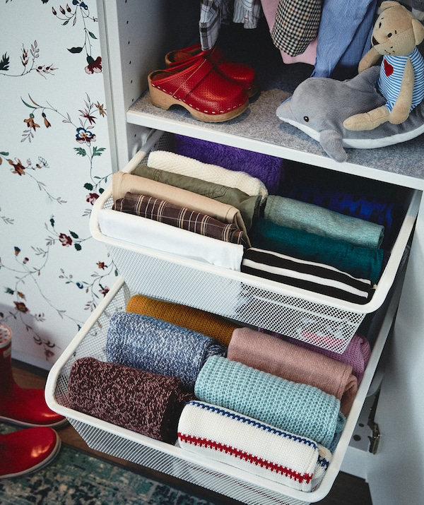 Dio garderobe s dvije djelomično otvorene ladice; obje su ispunjene uredno složenom odjećom organiziranom prema skupinama (ali ne u gomilama).