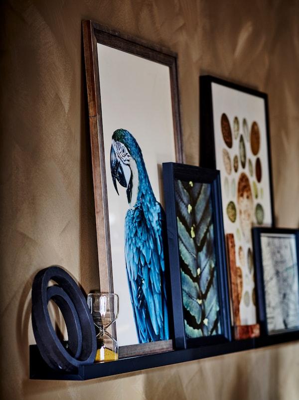 Dio smeđeg zida s crnom MOSSLANDA letvom za sliku s različitim ukrasnim predmetima i uokvirenim umjetninama.
