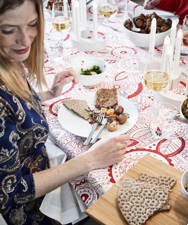 Dio ukrašenog blagdanskog stola s hranom, pićima i ljudima. Ženi je ponuđeno da odabere nešto s poslužavnika.