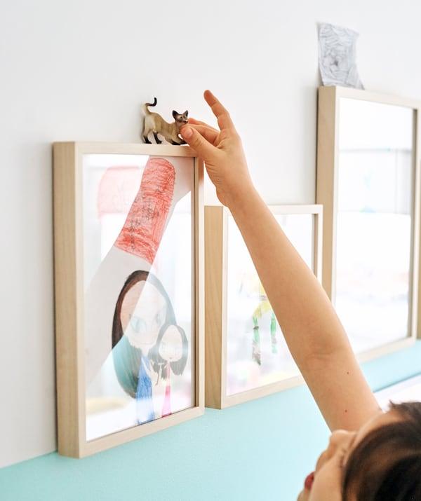 Disegni di bambini esposti in una serie di sottili cornici in legno. Una bambina appoggia un pupazzo a forma di gatto sulla prima cornice - IKEA