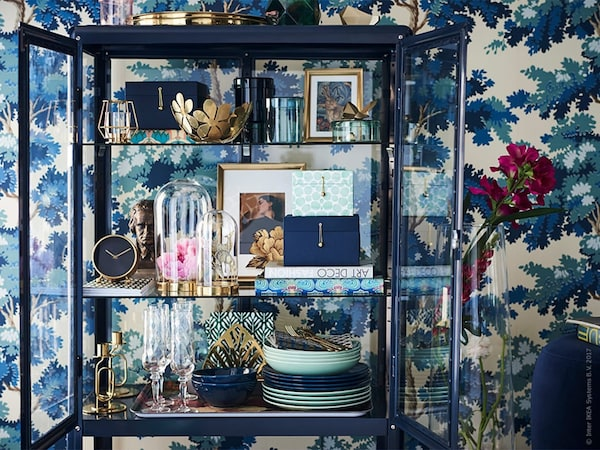 Display case in front of a wall with blue wallpaper
