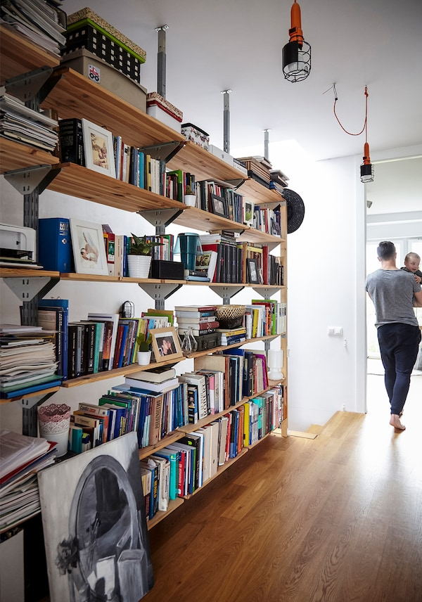 Display shelves in a hallway, loaded with books and boxes, with an adult holding a child walking down the corridor.