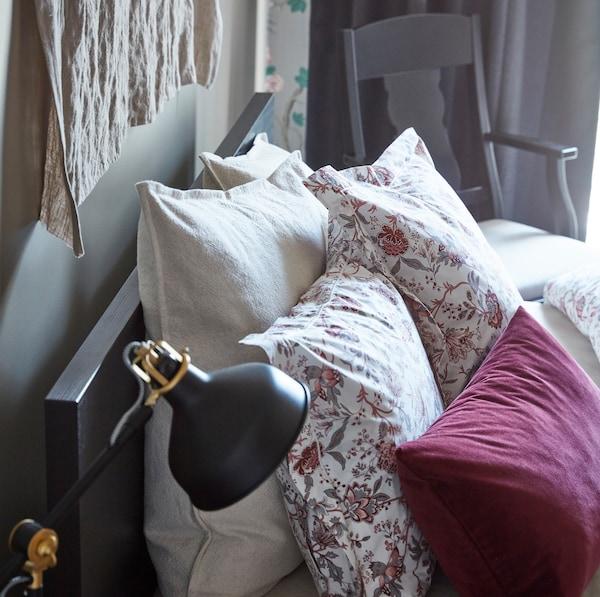 Díszítsd fel sötétbarna IKEA MALM furnér ágykeretedet puha textíliákkal és olyan díszpárnákkal, mint a virágmintás SPRÄNGÖRT és a sötétvörös bársony SANELA.