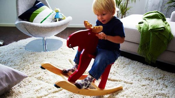 Dítě na červeném houpacím moose IKEA EKORRE vyrobeném z kaučukového dřeva ze zodpovědně obhospodařovaných lesů v Asii.