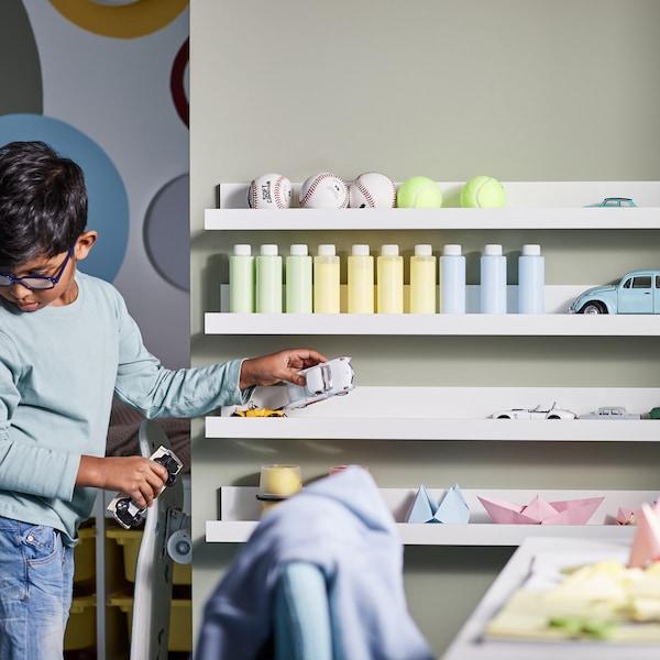 Dítě si hraje sautíčky vložnici, která má na stěně bílé police na obrázky MOSSLANDA spapírovými modely alahvemi.