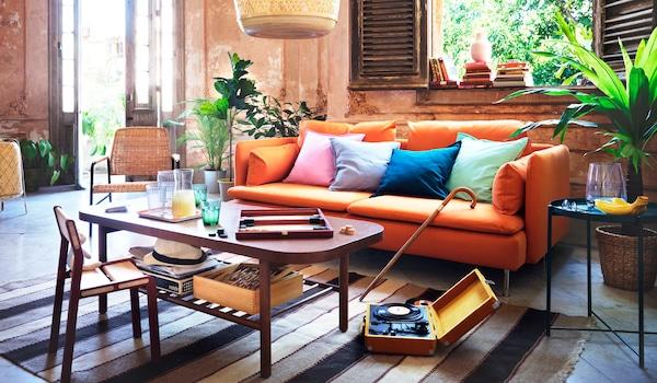 Divano SÖDERHAMN arancione con cuscini colorati. Di fronte, un tavolino con alcuni bicchieri e un gioco da tavolo - IKEA