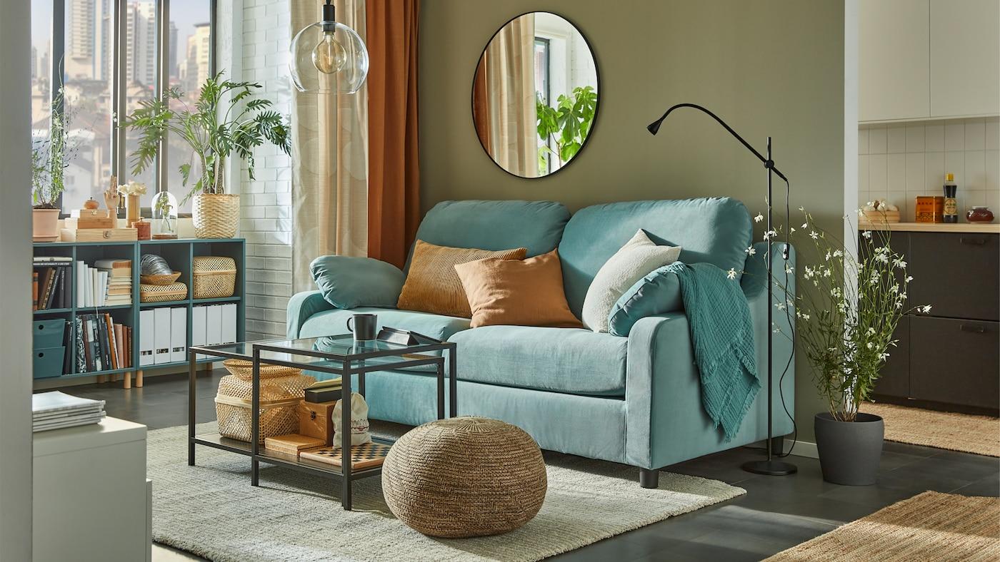 Divano turchese chiaro con schienale alto in un salotto verde/grigio illuminato dal sole, con mobili a giorno grigio/turchese accanto alla finestra.