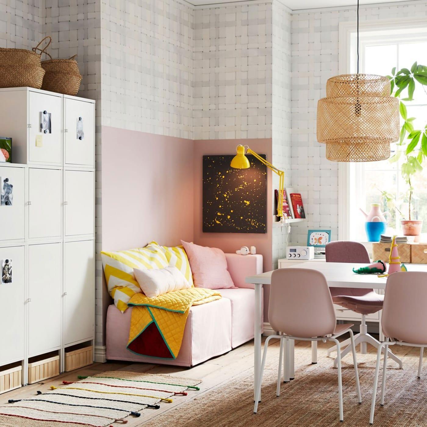 Diverse HÄLLAN Schränke in Weiss an einer Wand in einem kompakten Wohnraum in Rosa, Weiss und Gelb