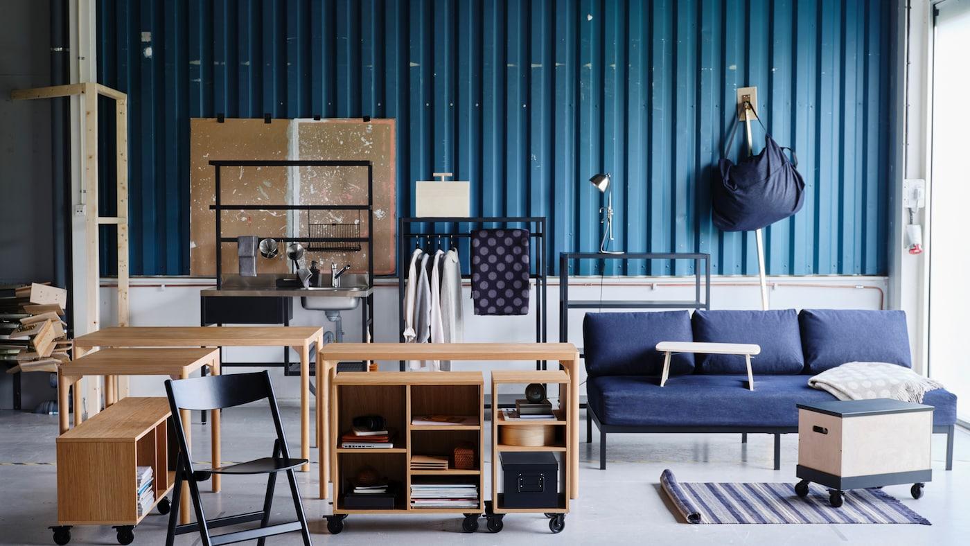 Diverse møbler fra RÅVAROR-serien, blant annet bord, ei dagseng og oppbevaringsløsninger mot en blågrønn bølgeblikkdekket vegg.